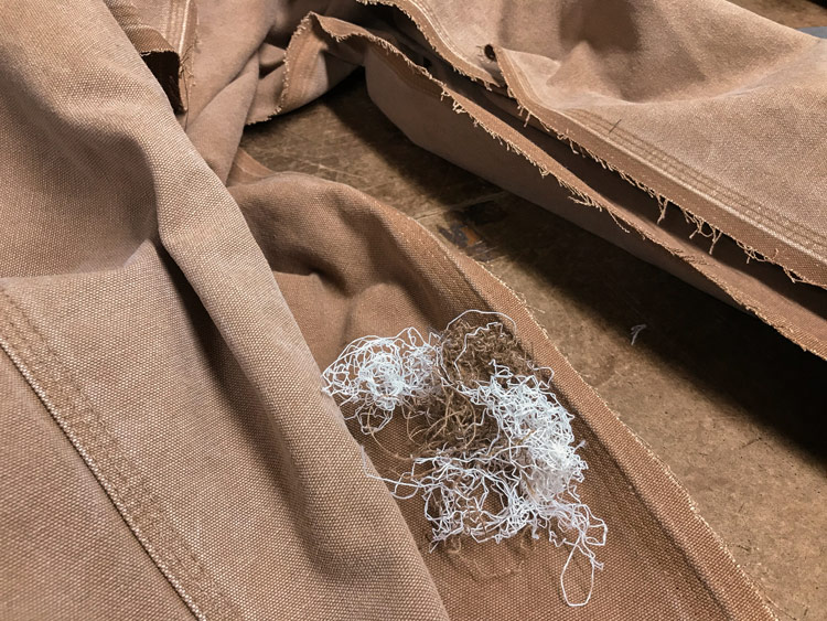 The 3-needle inseam stitching of carpenter pants is taken apart