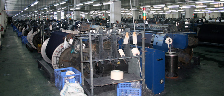 denim mill with rows of machines producing fabric in raw form