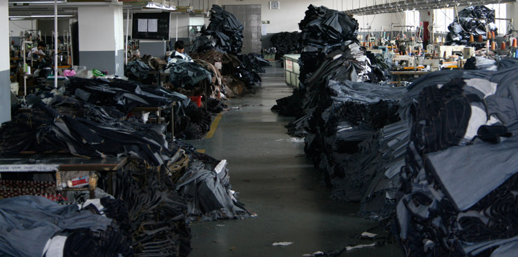 Stacks of raw jeans in sewing at a jeans factory will later go into washing