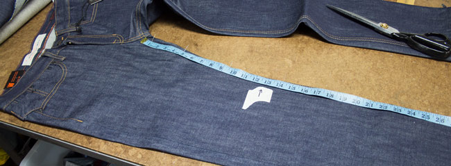 Example of a pair of Williamsburg raw denim jeans on cutting table with knee position marked for tapering