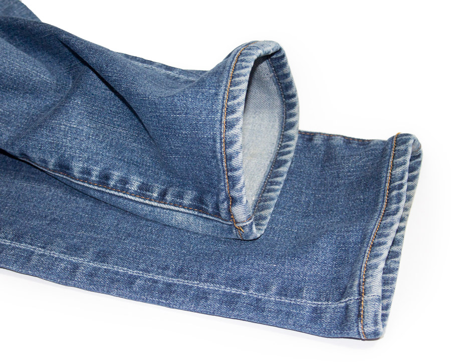 Close-up of light washed jeans with original hem alterations