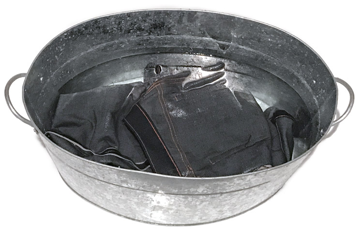 soaking raw denim jeans in a tub
